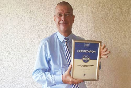 Jubilee Insurance Burundi CEO, Denis Huyberechts, possess for a picture after receiving the Blue Company Certification