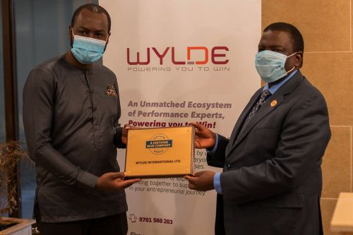 WYLDE International Chief Executive Officer, Joram Mwinamo, receiving the Blue Company Certification from Executive Advisory Board Member of the Blue Company, Dr. Julius Kipngetich